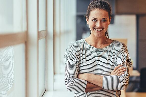 business casual woman crossing her arms and smiling