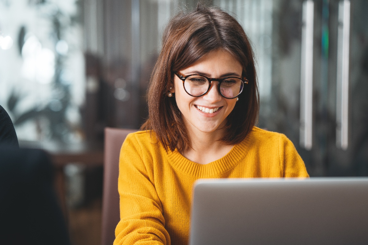 Happy woman in office looking at computer in glasses-1