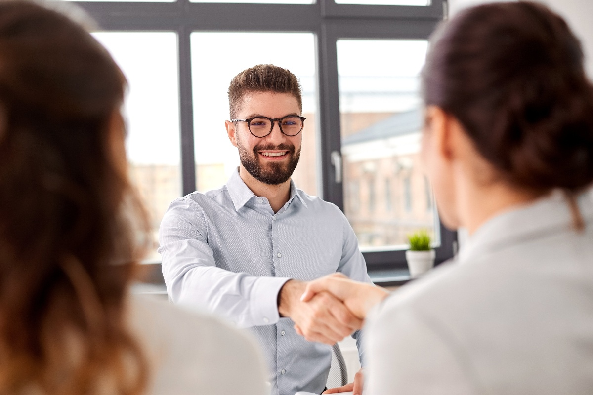 Man in glasses and button up shirt shakes hands with woman-1