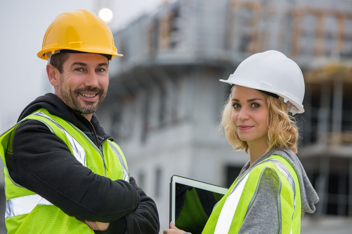 Two construction workers on site looking and smiling at camera-1