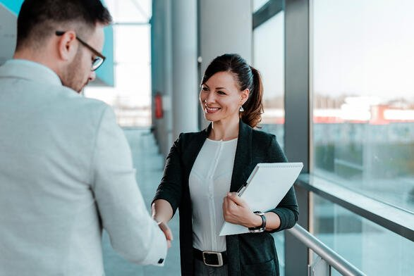 Woman in business outfit with clipboard shaking hands