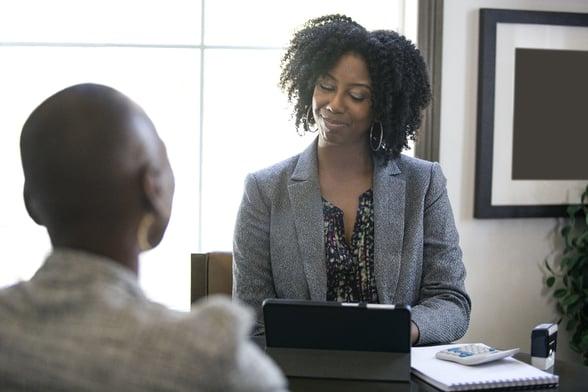 Woman in businesswear presenting to employee in office-1